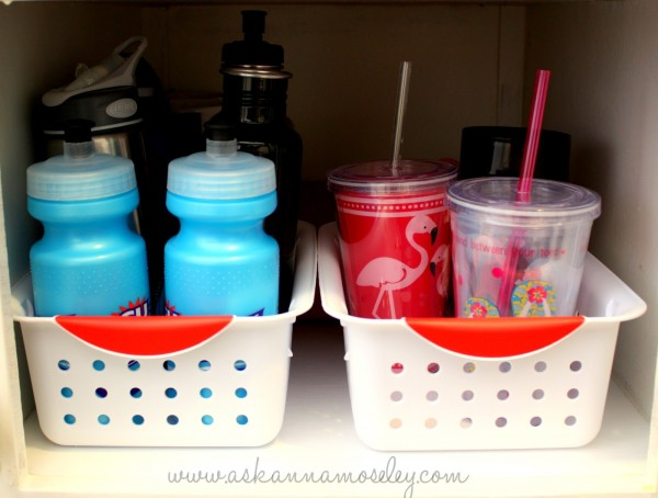 Organize water bottles with inexpensive baskets to keep them from falling over all the time - Ask Anna