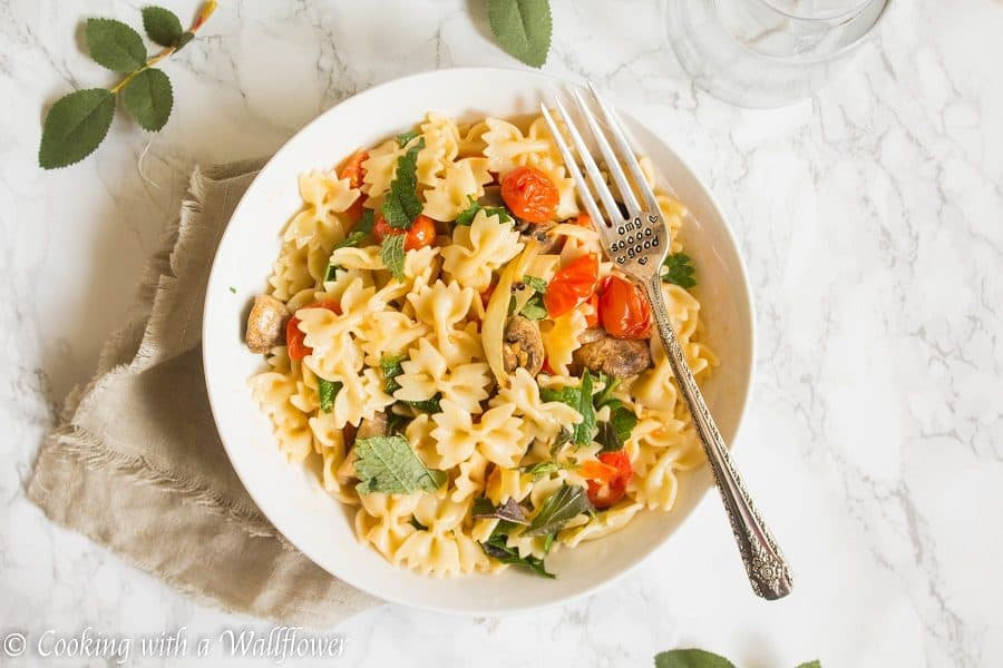 Bow tie pasta tossed with roasted mushrooms, tomatoes, onions, fresh herbs, and a drizzle of olive oil. This roasted mushroom tomato pasta is delicious, and a great choice for a quick and easy weeknight dinner | Cooking with a Wallflower