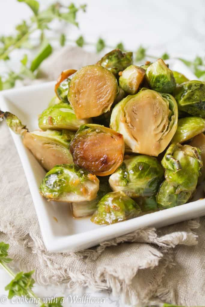 Brussels sprouts tossed in honey, sesame oil, and soy sauce then roasted until slightly charred. These roasted honey sesame brussels sprouts are delicious and a great side dish. | Cooking With a Wallflower